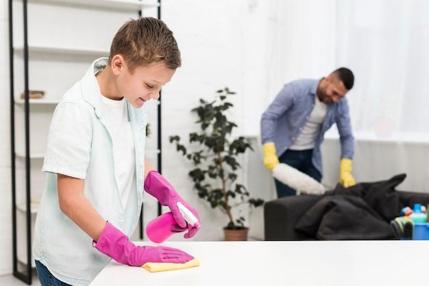 父親に沿って家を掃除する少年の側面図 無料写真