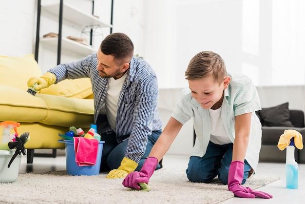 カーペットを掃除する父と息子 無料写真