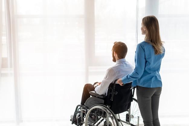 Взрослый мужчина и женщина, глядя в окно Бесплатные Фотографии