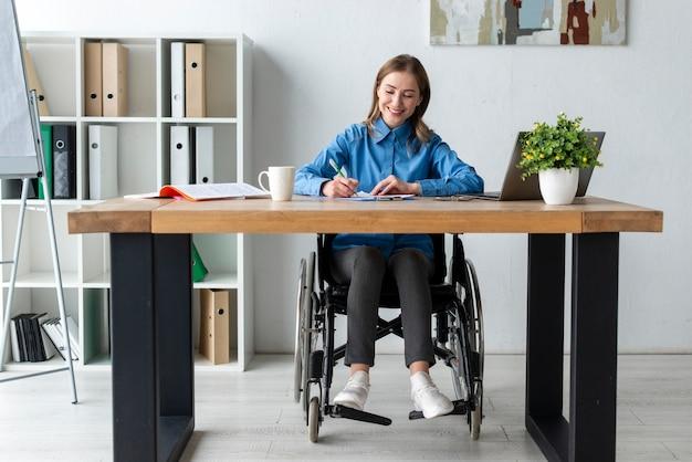 オフィスで働く肯定的な大人の女性 無料写真