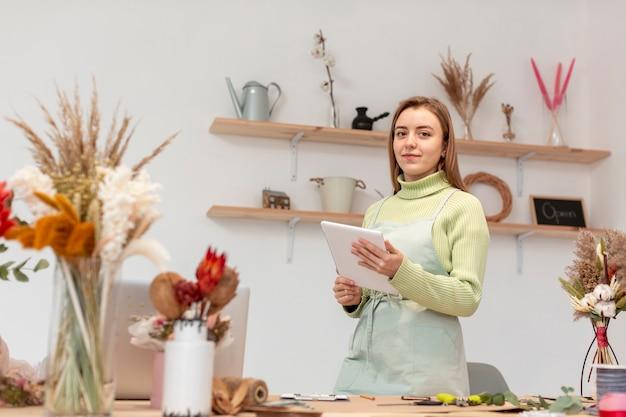 彼女自身の店でデジタルタブレットを保持しているビジネス女性 無料写真