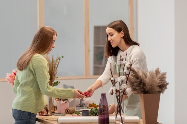 フラワーショップを配置するサイドビュービジネス女性 無料写真