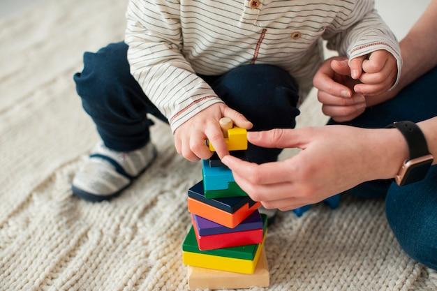 Высокий угол ребенка, играющего дома с матерью Бесплатные Фотографии