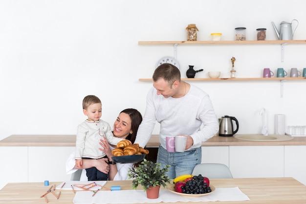 母親と父親が子供とコピースペースとキッチンで 無料写真