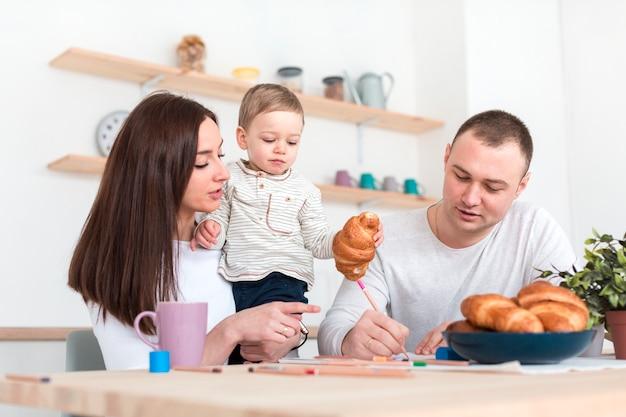 台所のテーブルで子供を持つ親 無料写真