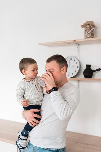 赤ちゃんを押しながらマグカップから飲む父 無料写真