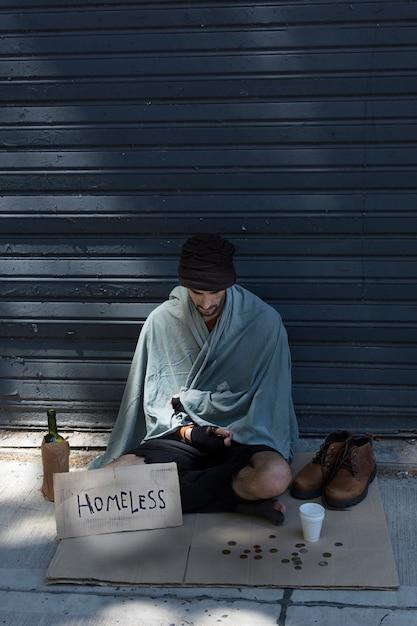 Бездомный мужчина с бутылкой алкоголя и монетами Бесплатные Фотографии