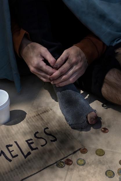Высокий взгляд нищего человека с монетами и отверстиями в носках Бесплатные Фотографии