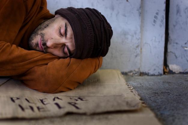 Бездомный человек спит на картоне Бесплатные Фотографии