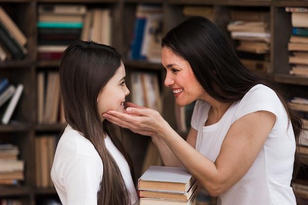 クローズアップの肯定的な女性と図書館で若い女の子 無料写真