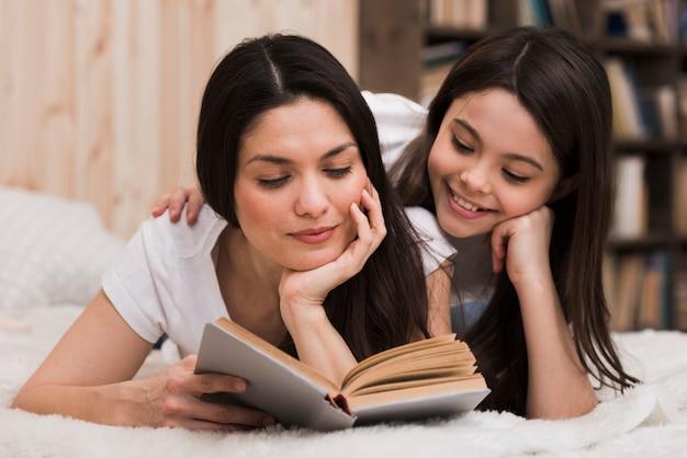 正面の大人の女性と本を読んでいる女の子 無料写真