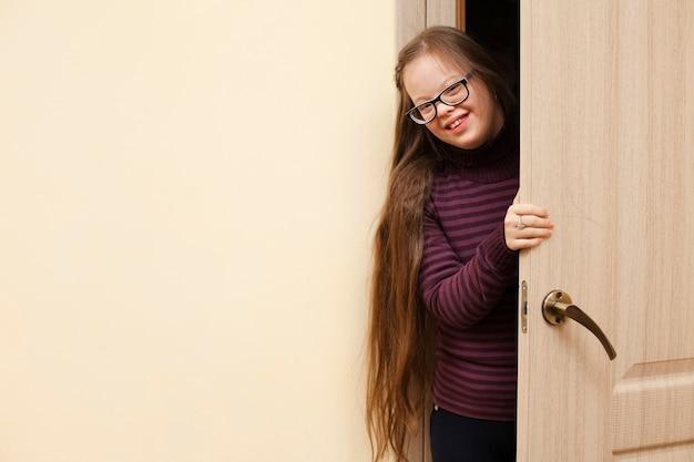 Улыбающаяся девушка с синдромом дауна позирует во время открытия двери Бесплатные Фотографии