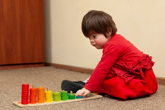 Вид сбоку ребенка с синдромом дауна играет Бесплатные Фотографии