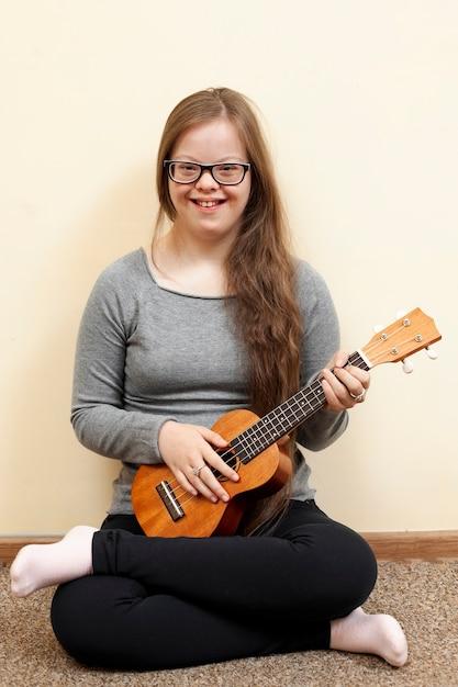 Девушка с синдромом дауна держит гитару и улыбается Бесплатные Фотографии
