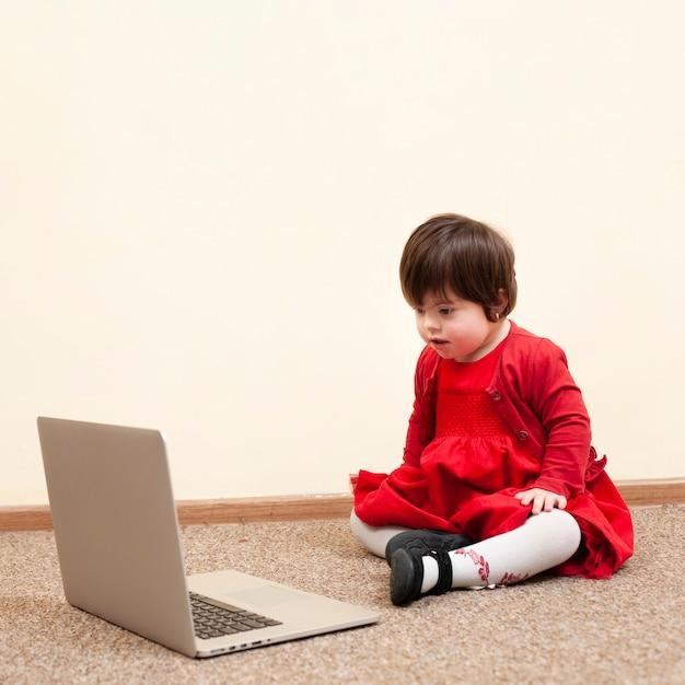 Ребенок с синдромом дауна смотрит на ноутбук Бесплатные Фотографии