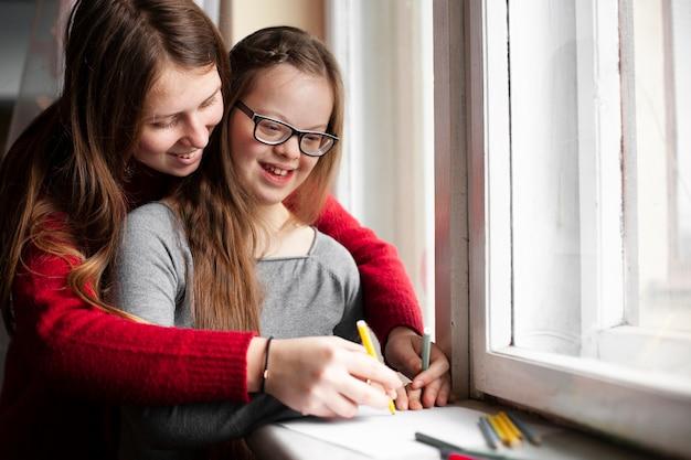 ダウン症候群を描くと幸せな女の子を持つ女性 無料写真