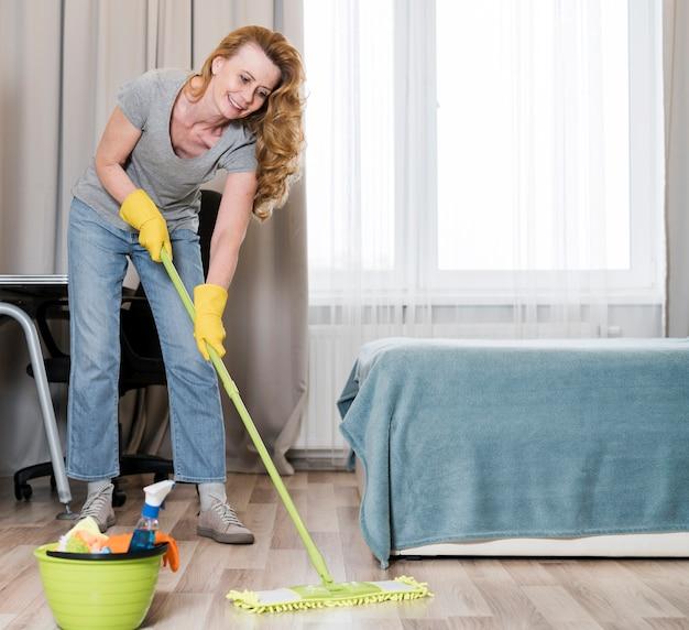 喜んで床を拭く女性の正面図 無料写真