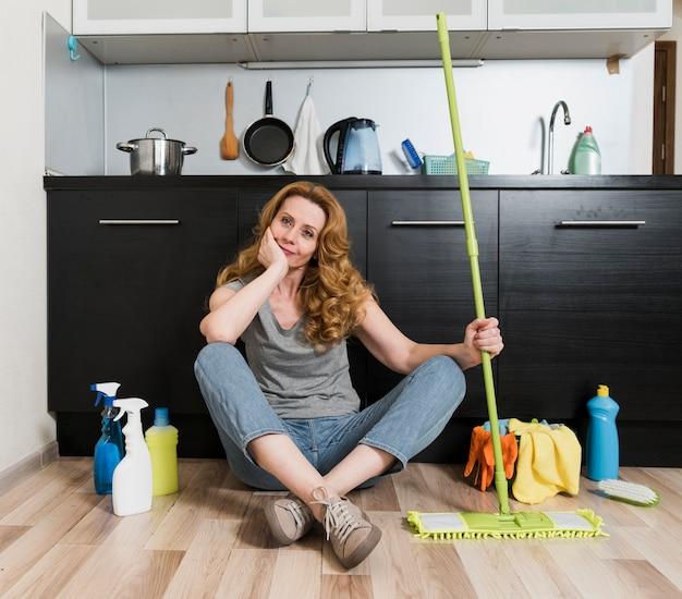 クリーニング製品とモップを保持している女性の正面図 無料写真