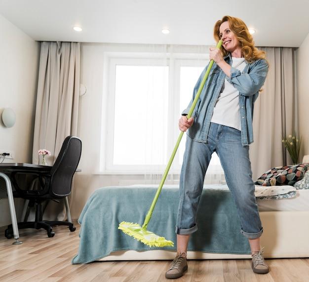 床を掃討しながら楽しんでいる女性 無料写真