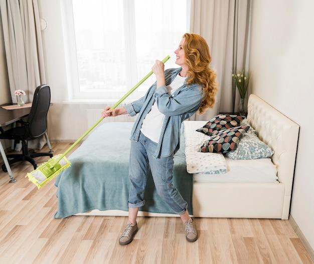 床を掃討しながら歌っている女性 無料写真