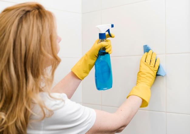シャワーの壁を掃除する女性の側面図 無料写真