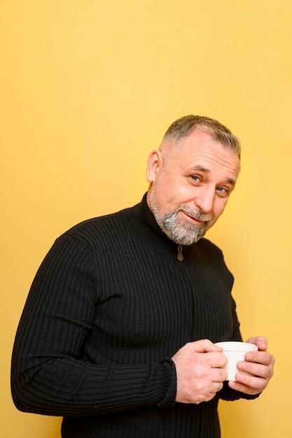 Зрелый человек держит чашку кофе рядом с желтой стеной Бесплатные Фотографии