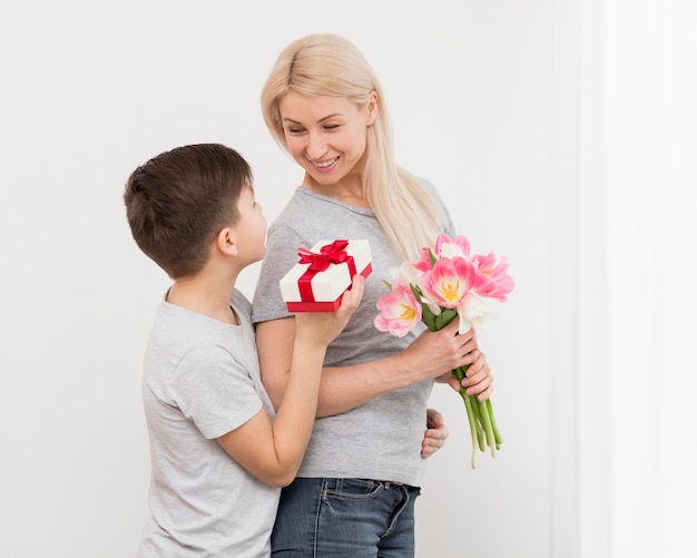 母への贈り物を提供するローアングルの息子 無料写真