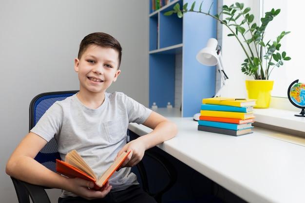 本と椅子の上の高角度の少年 無料写真