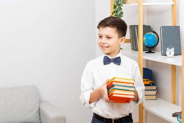 Улыбающийся маленький мальчик держит стопку книг Бесплатные Фотографии