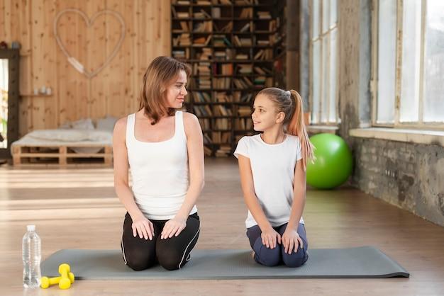 Мама и девушка сидят на коврик для йоги Бесплатные Фотографии