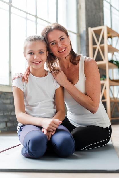 Дочь и мама позируют на коврики для йоги Бесплатные Фотографии