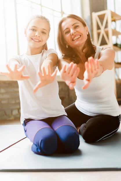 Милая дочь и мама позирует на коврики для йоги Бесплатные Фотографии
