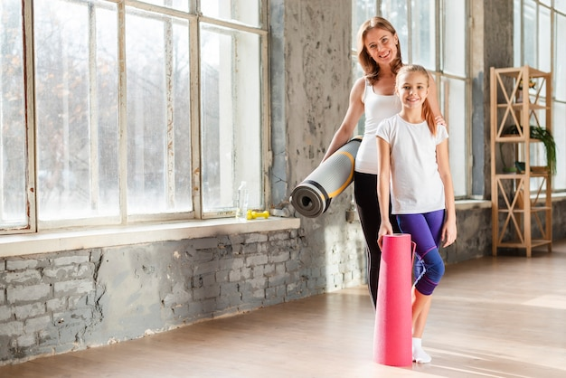 Полный выстрел мать и дочь, держа коврики для йоги Бесплатные Фотографии