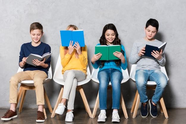 Дети на стульях читают Бесплатные Фотографии