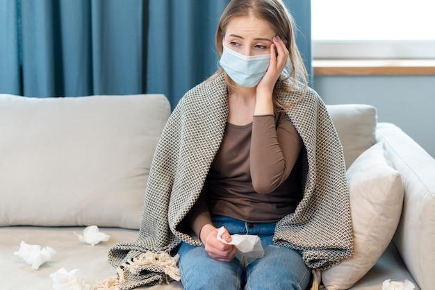 検疫に滞在し、熱を持っているマスクを持つ女性 無料写真