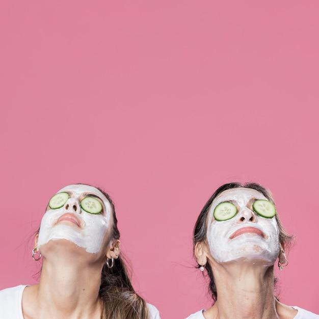 母と娘の顔のマスクを持つ 無料写真