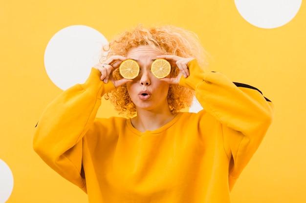 レモンスライスを持つ美しい少女の正面図 無料写真