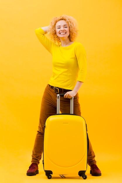スーツケースを持つ金髪の女性の完全なショット 無料写真