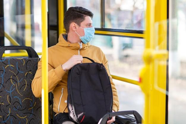 公共交通機関でサージカルマスクを持つ男 無料写真