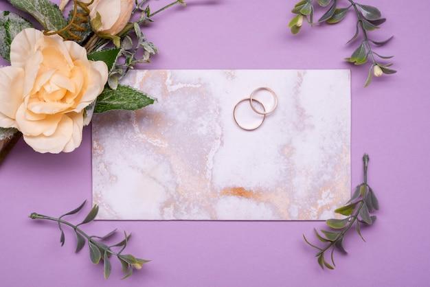 Вид сверху элегантного свадебного приглашения в окружении цветов Бесплатные Фотографии