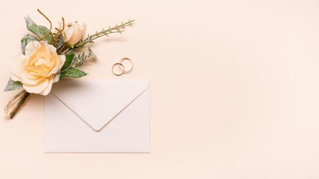 Вид сверху на свадебные приглашения с обручальными кольцами Бесплатные Фотографии