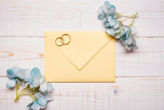 Элегантные обручальные кольца на столе с цветами Бесплатные Фотографии