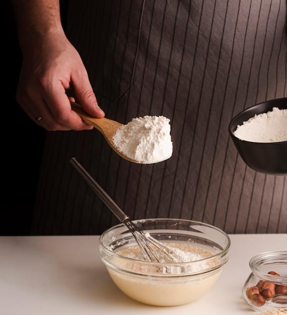 Мужской повар добавить муку в смесь Бесплатные Фотографии