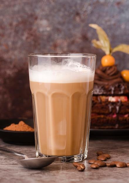 Вид спереди стакан шоколадного молока с ложкой и кофейных зерен Бесплатные Фотографии