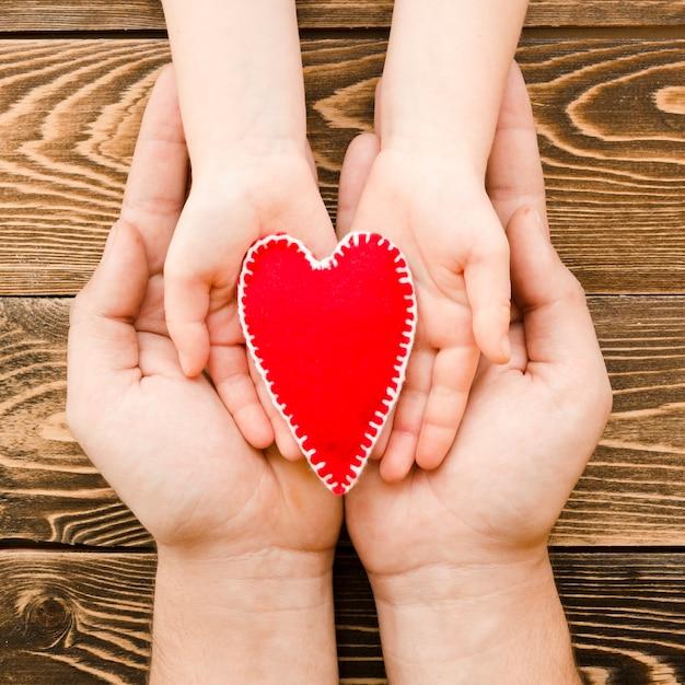 Люди, держащие красное сердце в руках на деревянном фоне Бесплатные Фотографии