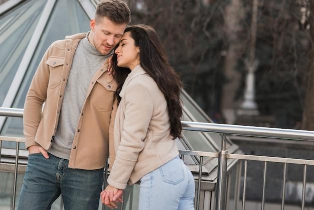 Милая пара, держась за руки снаружи Бесплатные Фотографии