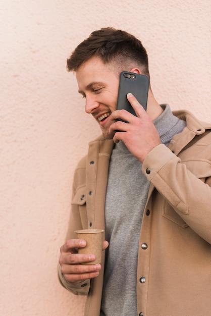 Красивый мужчина разговаривает по телефону и держит чашку кофе Бесплатные Фотографии