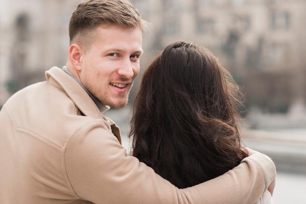 Мужчина обнимает женщину во время позирования Бесплатные Фотографии
