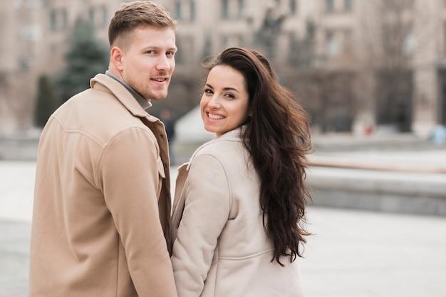 Улыбающаяся пара позирует на улице Бесплатные Фотографии