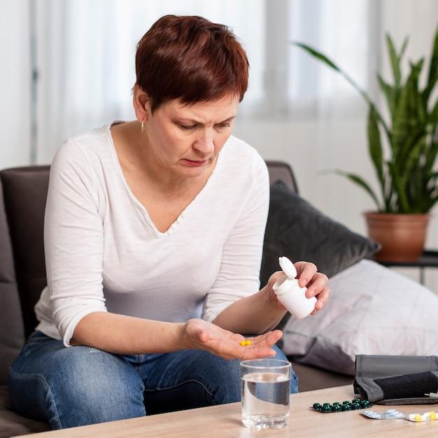 薬を服用している女性の正面図 無料写真